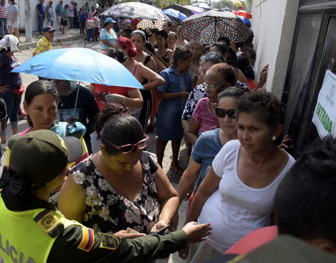 Una policía dirige a los votantes que esperan su turno para entrar al puesto de votación.
