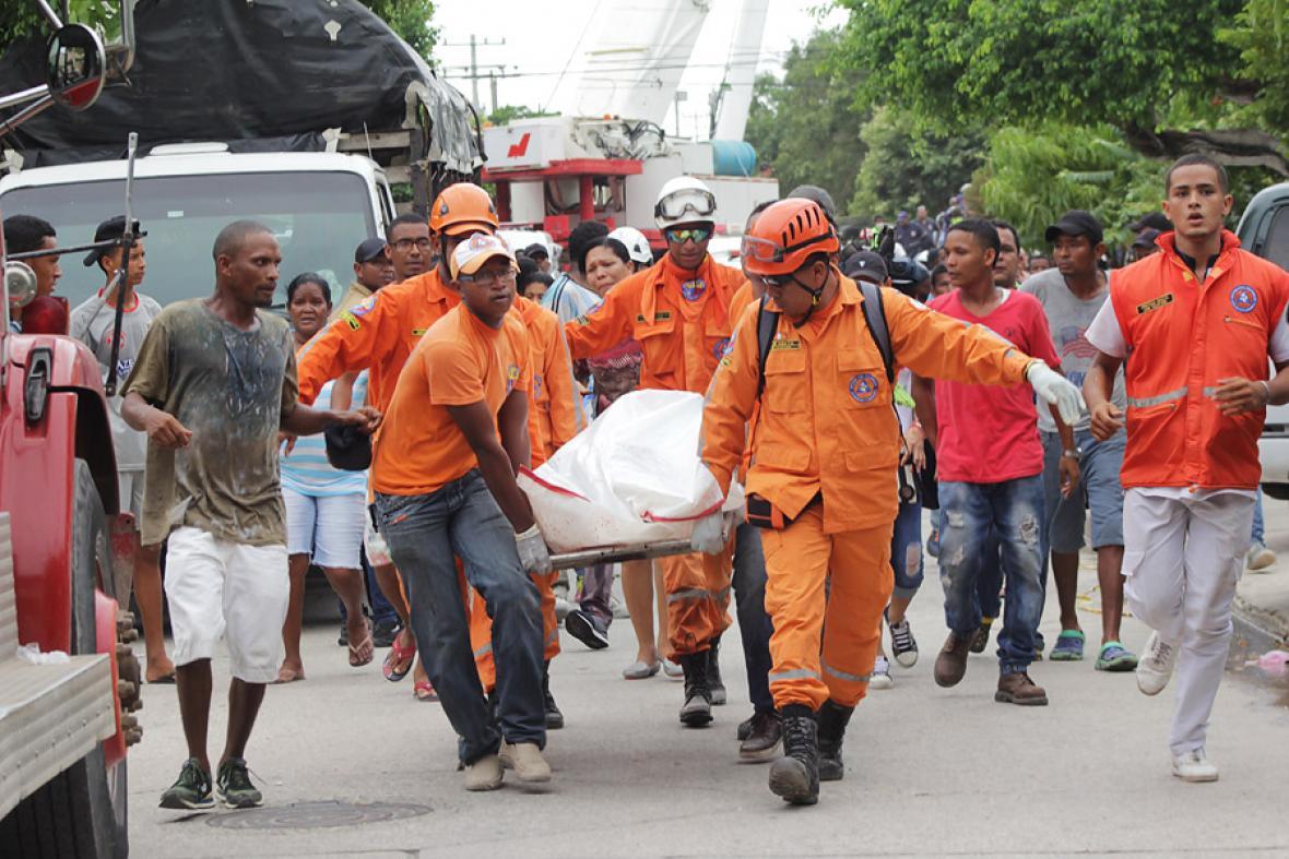 Cuatro rescatistas de Defensa Civil, cargan a uno de los cinco cuerpos que dejo el desplome del edificio.