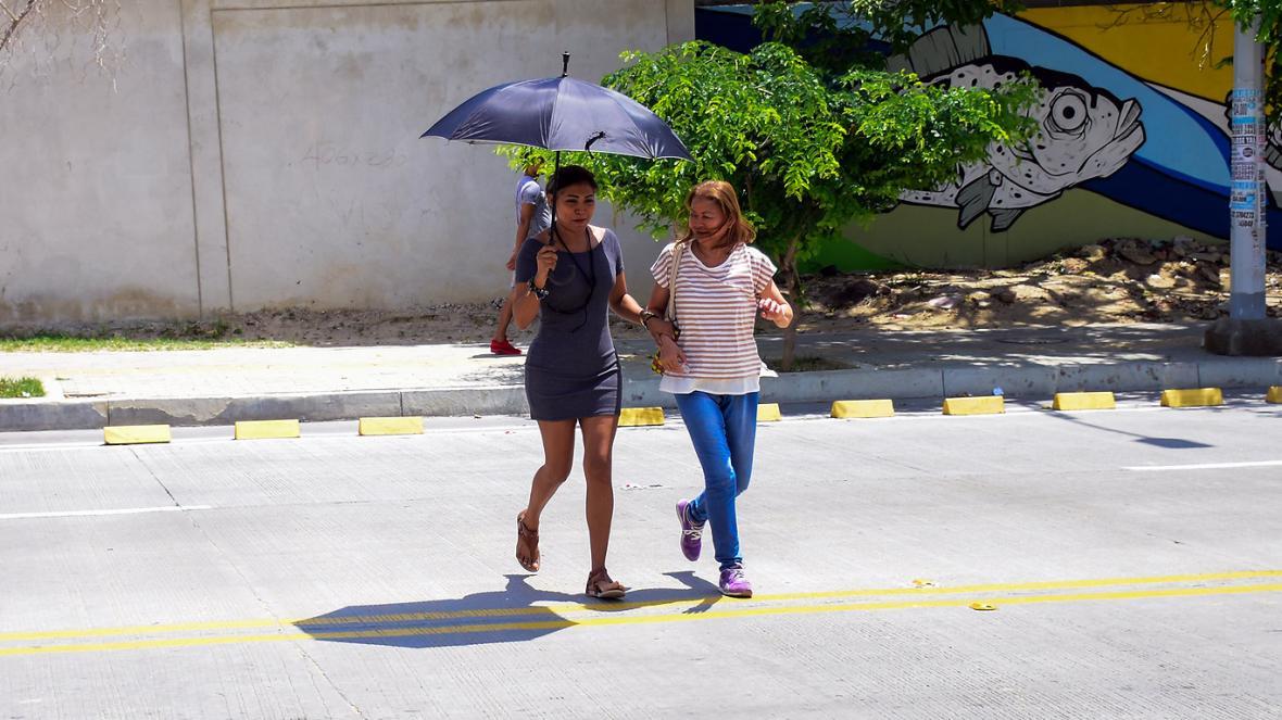 Dos mujeres corren para no ser alcanzadas por un vehículo.