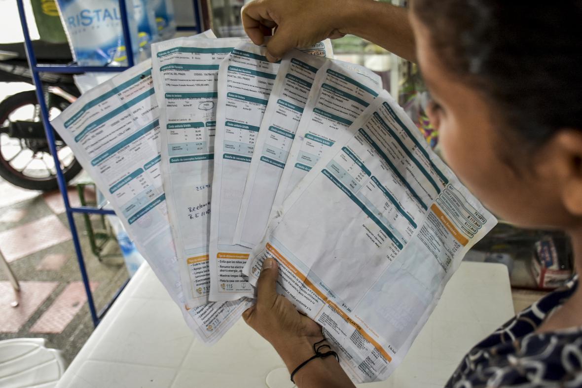 Una usuaria muestra varias facturas de Electricaribe.
