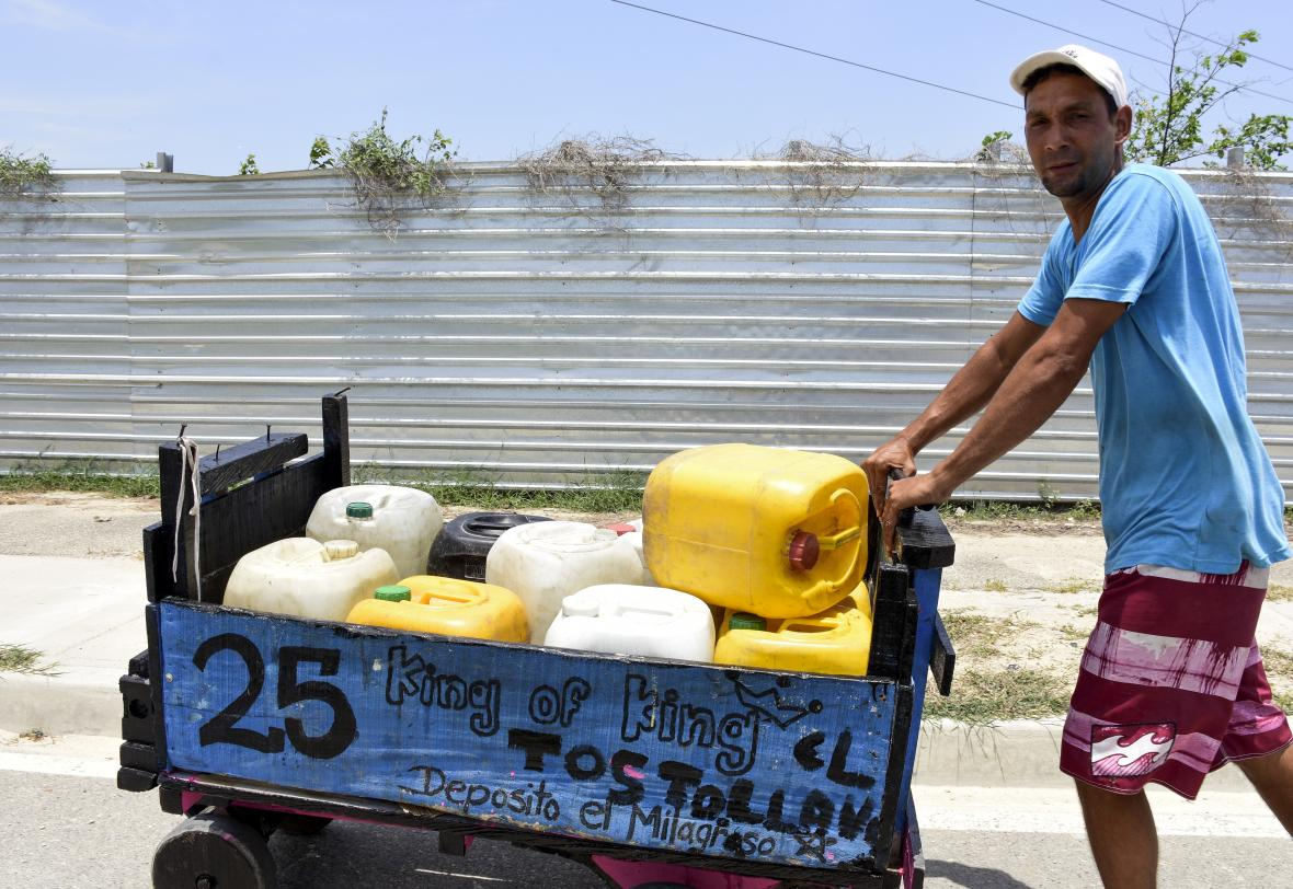 One of the residents of the La Luz district moved several plastic containers to get water.
