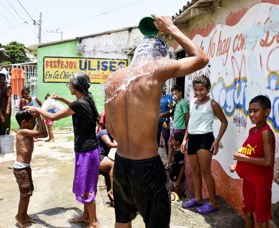 Niños y jóvenes aprovechan el tubo madre destapado para bañarse en la calle por la falta de líquido.