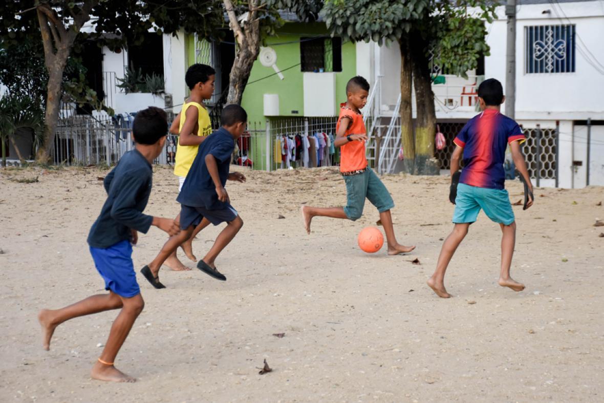 Niños de 7 de Abril juegan fútbol en una cancha cubierta de arena.