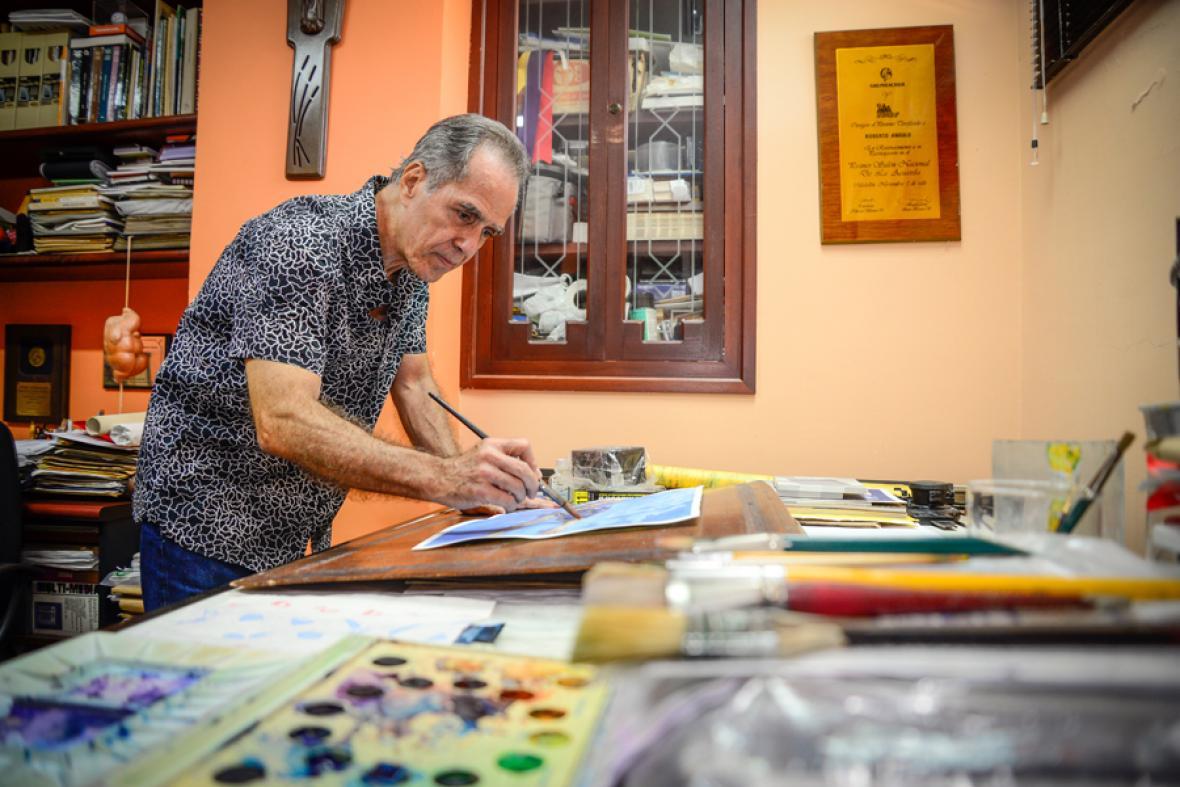 El artista tiene adecuada su oficina para la pintura en acuarela.