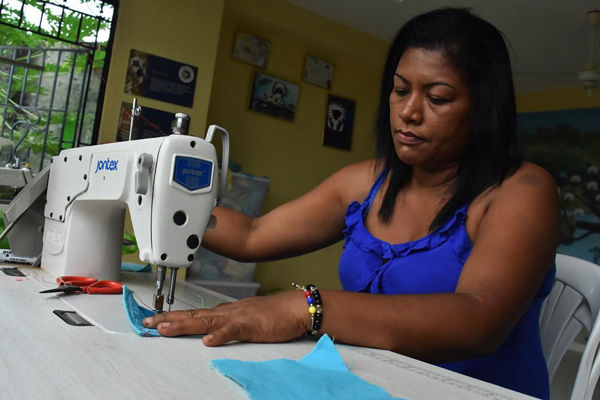 Claudia Valencia cose en una máquina la pieza de uno de los bolsos.