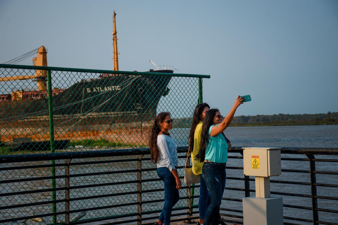 Tres jóvenes se toman una selfi en el Gran Malecón. Al fondo se aprecia el barco B Atlantic.