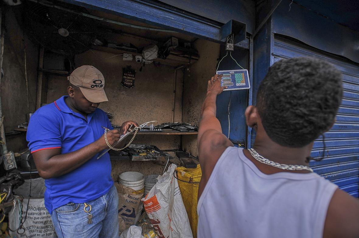 Dos hombres calculan desde la balanza digital.