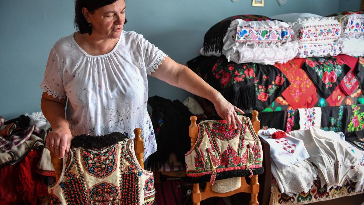 Dorina Hanza, una bordadora de 52 años, muestra dos trajes tradicionales de la región noroeste de Bihor en Rumania.
