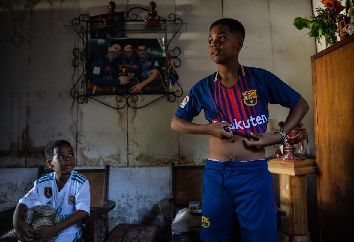 Dos niños cubanos reflejan su afición por dos de los grandes clubes del mundo, Real Madrid y Barcelona.