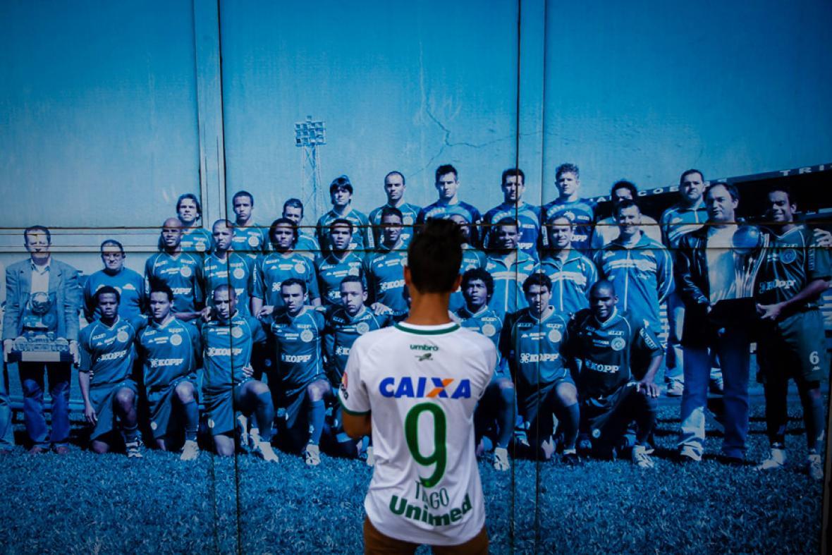 Un hombre observa la foto del equipo Chapecoense a la entrada del estadio de fútbol en donde está prevista una vigilia.