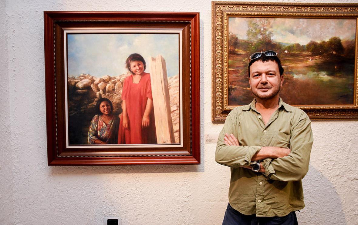 El artista Gustavo Anaya junto con su exposición.