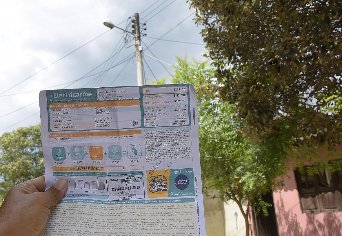Un habitante de Juan de Acosta muestra su recibo de energía en donde está incluida la tarifa de alumbrado.