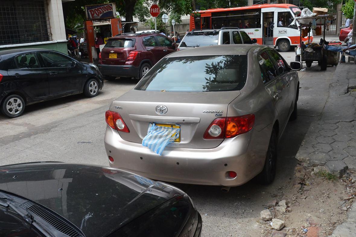 Con una bolsa plástica tapan las placas de este auto mal estacionado en la calle 38b con carrera 45.