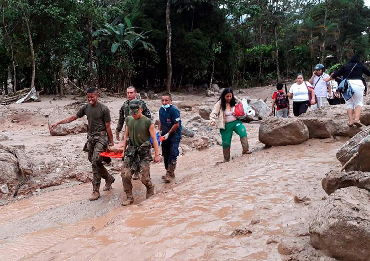 Soldados conducen a una persona herida en medio del lodo y la lluvia que no han cesado en Mocoa.