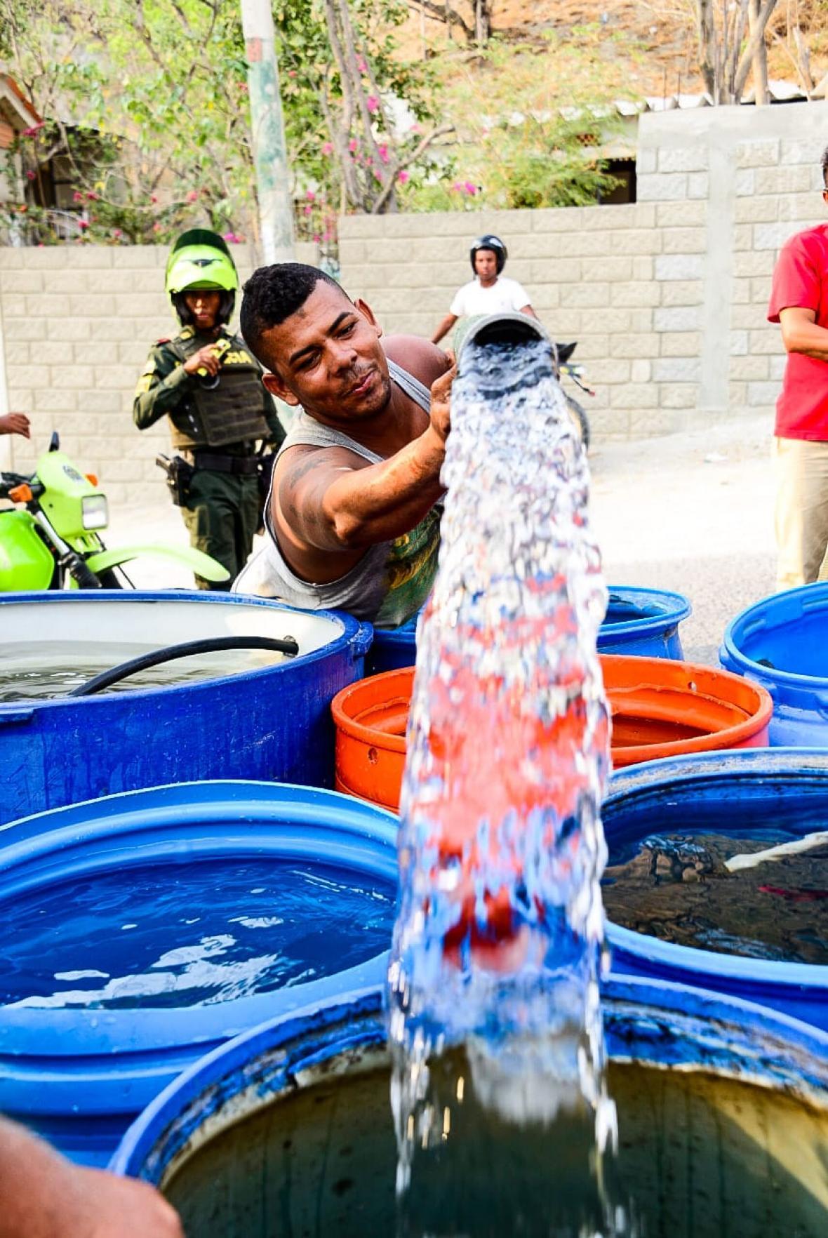 Hombre recolecta agua del carrotanque.