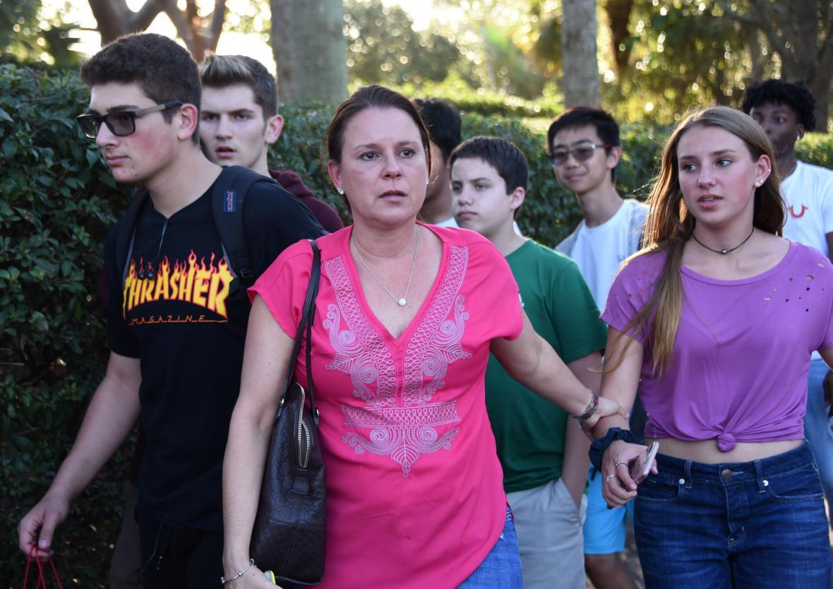 Estudiantes salen con familiares de la escuela Marjory Stoneman Douglas High School de Florida tras el tiroteo de este miércoles.