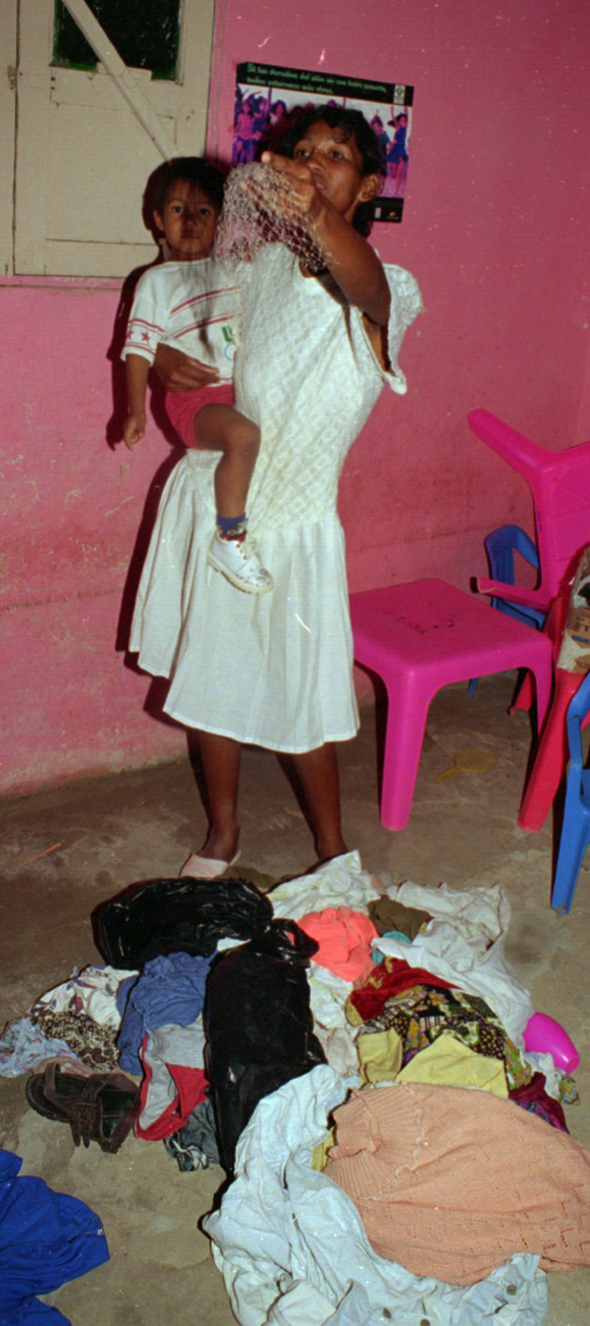 Una mujer muestra los trapos que le sacaron.