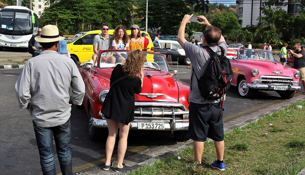Varios turistas se toman fotos en unos autos antiguos en La Habana.