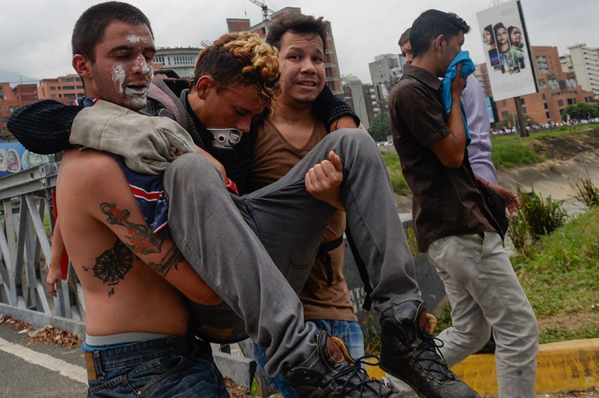 Una persona herida es conducida por otras dos durante las marchas de este jueves.