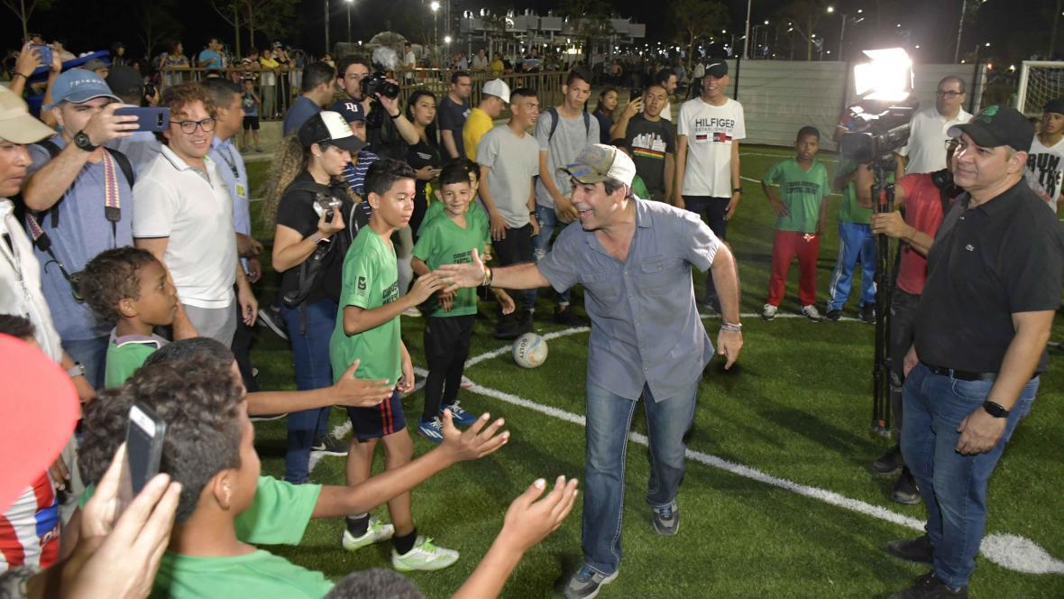 Alejandro Char, alcalde de Barranquilla, saluda a niños que juegan fútbol  en las nuevas canchas que están en el Gran Malecón.