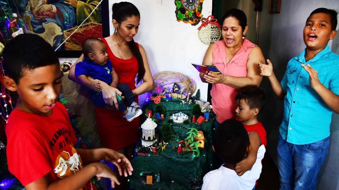 Familia reunida alrededor del pesebre para celebrar la tradicional novena de aguinaldos.