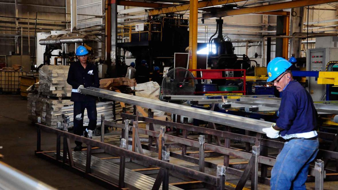 Dos trabajadores desarrollan su labor en la planta de la empresa Tecnoglass en Barranquilla.