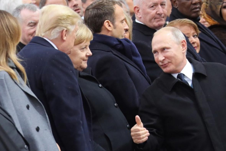 Trump y Putin hablan momentos previos a los actos oficiales en París. Los acompaña la canciller alemana Ángela Merkel.