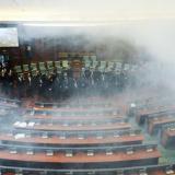 Miembros de la oposición nacionalista albanokosovar lanzan gases lacrimógenos en el Parlamento de Kosovo.