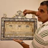 Enrique Yidi, director de la muestra de la exposición en nácar, sosteniendo una pieza.