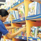 Una empleada acomoda los cuadernos en un estante.