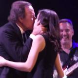Momentos en que Iglesias besa a la fan en el escenario.