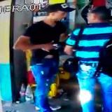 Momento en el que uno de los delincuentes intimida con un revólver al periodista, en la tienda.