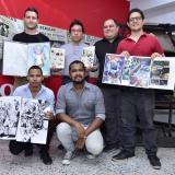 Participantes presentan el arte que expondrán.