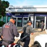Policías vigilan la sede bancaria atracada este lunes en Riohacha.