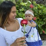 Katiana Ojeda sonríe a su hija de 8 meses, Salomé Romero, mientras le muestra una rosa que le obsequiaron.