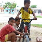 Los primos Hernández juegan con una bicicleta en la puerta de su vivienda, en La Paz.