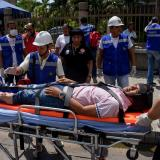 Rescatistas trasladan en una camilla a unos de los supuestos heridos.