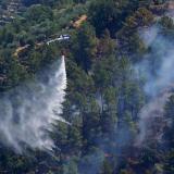 Un helicóptero de combate contra incendios deja caer agua sobre un incendio en la aldea de Alijo, Portugal.