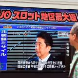 Un peatón escucha atento las declaraciones del primer ministro japonés Shinzo Abe tras el  lanzamiento de un misil por parte de Corea del Norte.