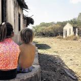 Dos niños miran a lo lejos en una polvorienta calle del corregimiento de Santa Rita, Magdalena.