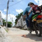 Un hombre y un niño en moto suben la popular loma de Mequejo, que da la bienvenida al barrio.