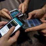 Personas utilizan sus celulares.