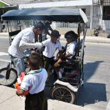 El conductor de un bicitaxi ayuda a un niño a bajar de su vehículo, frente a un colegio en Las Nieves.