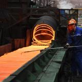 Trabajador de una empresa del sector productor de acero opera la maquinaria.
