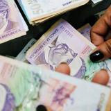 Ciudadana sosteniendo una cantidad de billetes de 50.000 pesos.