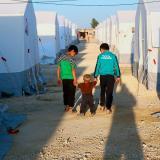 Tres niños sirios caminan en un campamento para desplazados en al-Bil, en el norte de Siria.