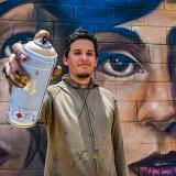 Jean Betancourt, conocido como Mr. Garek, muestra una lata de pintura frente a su mural, ubicado en la Vía 40 con calle 78.