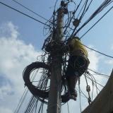 Un hombre arriesga su vida en medio de cables.