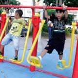 Dos niños se recrean en un juego infantil del parque.