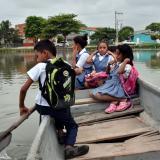 Jhon rema en la zona izquierda de la canoa mientras sus compañeras de Brisas del Río miran el panorama.